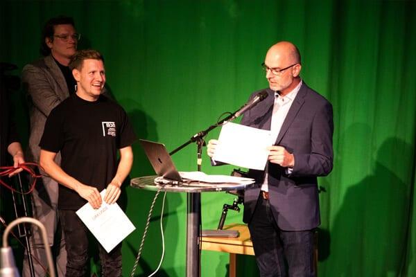 Stellvertretender Bezirksvorsteher Herr Andreas Heintzeler hält seine Rede zum Vereinsjubiläum der Medienwerkstatt, daneben steht der 1. Vorsitzende und Oliver Brixel