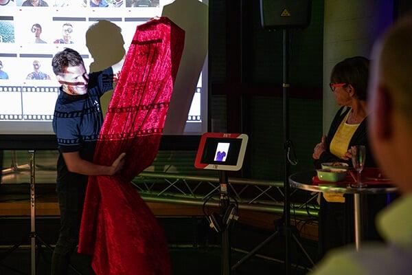 Der erste Vorsitzende enthüllt die Video-Stele, welche das Jubiläumsvideo zeigt und in der Bücherei in Zukunft ausgestellt wird